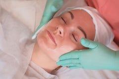 La fille passe par des traitements faciaux dans le salon de beauté Gants de port d'esthéticien appliquer la crème hydratante sur  photo libre de droits