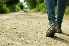 La fille passe sur un chemin de terre par les arbres Photos libres de droits