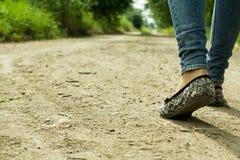 La fille passe sur un chemin de terre par les arbres Images libres de droits