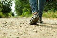 La fille passe sur un chemin de terre par les arbres Photos stock