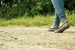 La fille passe sur un chemin de terre par les arbres Image libre de droits