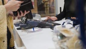 La fille paye au contrôle dans le magasin d'habillement du ` s de femmes Photo libre de droits