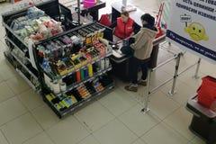 La fille paye les marchandises au checkout dans un magasin de matériel photo libre de droits