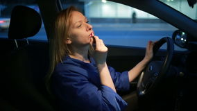 La fille peint des lèvres avec un lustre de lèvre, se reposant à la roue d'une voiture clips vidéos