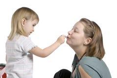 la fille peint des languettes à la momie Image stock