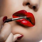 La fille peint des languettes avec le rouge à lievres images libres de droits