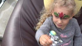La fille peinte blonde de visage sucent la sucrerie sur le bâton se reposant sur le fauteuil poire Mouvement de cardan clips vidéos
