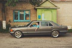 La fille pendant les années 90 est au sujet des voitures Photos stock