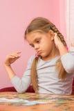 La fille pense rassemblant des puzzles de photo Image libre de droits