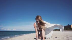 La fille, plage, mer, vent dans votre belle fille des cheveux A dans un bikini coloré et un manteau blanc transparent, s'assied s banque de vidéos