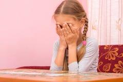 La fille pleure couvrant son visage de ses mains rassemblant la photo des puzzles Image libre de droits