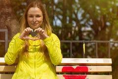 La fille a plié ses doigts sous forme de coeur Photo stock