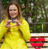 La fille a plié ses doigts sous forme de coeur Photographie stock