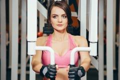 La fille pompe les groupes principaux de muscle dans le gymnase Formation de force Forme physique femelle Fille intense photographie stock