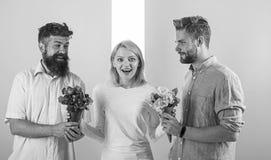 La fille populaire suscitent l'attention d'hommes de sort Le sourire de femme ne peut pas choisir l'associé, saisit les deux bouq photos libres de droits