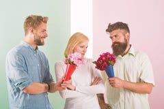 La fille populaire suscitent l'attention d'hommes de sort Les concurrents d'hommes avec l'essai de fleurs de bouquets conquièrent images stock