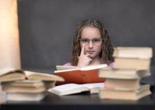 La fille a porté des verres et lire un livre photos stock