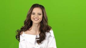 La fille pose pour les appareils-photo, elle redresse ses cheveux, cligne de l'oeil et flirte Écran vert banque de vidéos