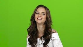 La fille pose pour les appareils-photo, elle sourit admirablement, cligne de l'oeil et flirte Écran vert Mouvement lent banque de vidéos