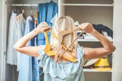 La fille près d'une garde-robe avec des vêtements ne peut pas choisir quoi porter Le concept bien choisi lourd n'a rien à porter images libres de droits