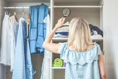 La fille près de la garde-robe avec des vêtements regarde avec une loupe qu'elle devrait utiliser Concept bien choisi lourd rien  images stock