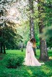 La fille près des arbres verts et de l'Apple blanc de floraison corrige la longue robe image libre de droits
