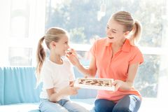 La fille a préparé une surprise pour sa mère La fille a donné à mère une boîte de chocolats Images stock