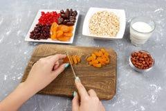 La fille prépare ses fruits secs par coupe de petit déjeuner dans le gruau de farine d'avoine sur une planche à découper Petit dé photographie stock libre de droits