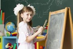 La fille préscolaire dessine sur le tableau noir photo stock