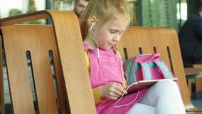 La fille préscolaire utilise des écouteurs et un comprimé d'ordinateur dehors temps léger de jour clips vidéos