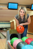 La fille prend la bille de deux mains pour jouer au bowling Photo libre de droits