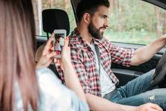 La fille prend la photo de son ami bel Il regard du ` t de doesn sur l'appareil-photo mais poser et conduire la voiture Photo stock