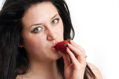 La fille prend un dégagement d'une fraise photographie stock