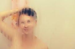 La fille prend une douche dans la salle de bains Photo libre de droits