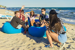 La fille prend une photo du groupe d'amis sur la plage Photo stock