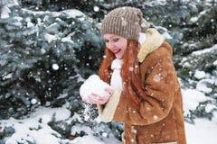 La fille prennent une poignée de neige en parc d'hiver au jour Sapins avec la neige Photos stock