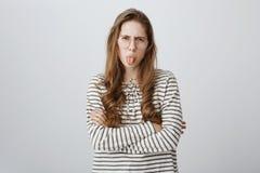 La fille puérile exprime son aversion, étant impolie et grossière Portrait de fille contrariée attirante dans transparent photos stock