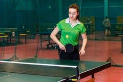 La fille quinze de l'adolescence an joue la boule dans le ping-pong image stock