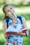 La fille réfléchie joyeuse se tient en parc d'été avec le cahier de croquis et le crayon de couleur dans des mains, portrait photos stock