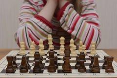 La fille réfléchit sur le premier mouvement d'échecs photographie stock