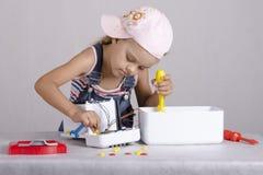 La fille répare de petits appareils ménagers de jouet Images stock