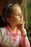 La fille rêvant à un hublot Image stock