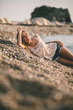 La fille rêveuse détendent sur la plage dans des chemises de jeans de mode Photographie stock
