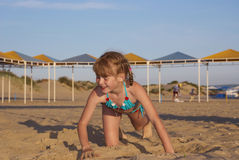 La fille rampe sur le sable de plage Photos stock