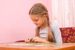 La fille rassemblent heureusement des puzzles de photo Photos libres de droits
