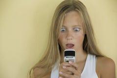 La fille reçoit le message étonnant de téléphone portable photo stock