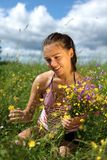La fille recueille des fleurs dans un domaine Photos stock