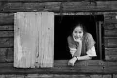 La fille regarde à l'extérieur l'hublot photo stock