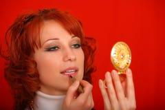 la fille regarde dans le miroir et le rouge à lèvres Images libres de droits
