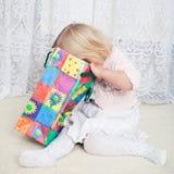 La fille regarde dans le sac à provisions Photo libre de droits